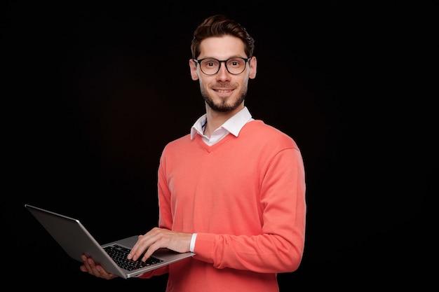 Portret pewny siebie młody informatyk z zarostem stojącym na czarnym tle i korzystającym z nowoczesnego laptopa
