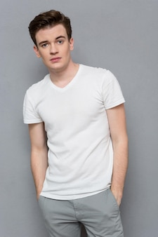 Portret pewny siebie poważny zamyślony młody człowiek w białej koszulce i szarych spodniach na szarej ścianie