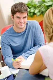 Portret pewny siebie uczeń pracuje z jego przyjacielem w bufecie