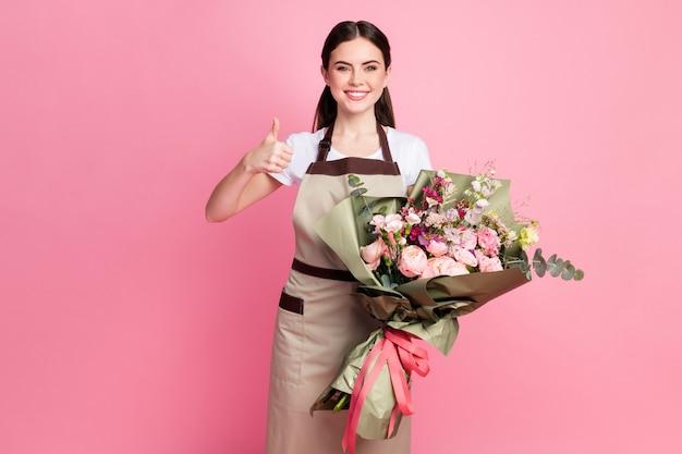 Portret pewny siebie właściciel sklepu trzymającego kwiaty ślubne pokazując kciuk do góry