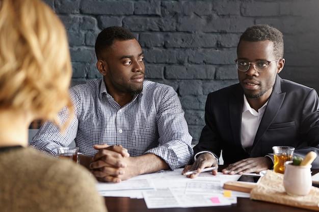 Portret pewnych siebie i odnoszących sukcesy biznesmenów afroamerykańskich zatrudniających nowego księgowego w swojej firmie
