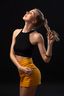 Portret pf młoda piękna blondynki kobieta pozuje w moda koloru żółtego spódnicie i rzemiennym żakiecie na czarnym odosobnionym tle.