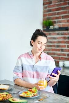 Portret pf uśmiechnięta młoda kobieta cieszy się śniadaniem w domu i sprawdza media społecznościowe
