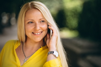Portret piękna blondynki dziewczyna opowiada na telefonie