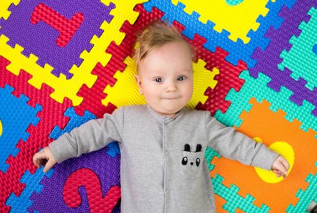 Portret pięciomiesięcznego chłopca na jasnym, wielobarwnym dywanie