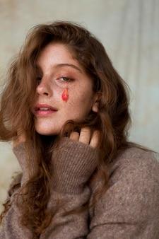Portret piegowatej kobiety z liśćmi na twarzy