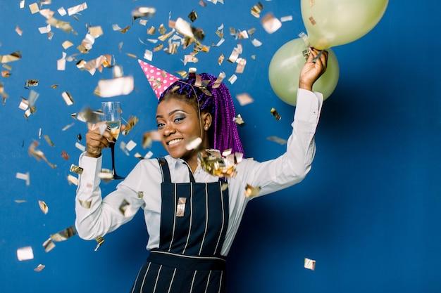 Portret piękna afrykańska dziewczyna trzyma lotniczych balony i szampana w różowej partyjnej nakrętce, odpoczywa przy przyjęciem. afrykańska kobieta ma zabawę przy przyjęciem z confetti na błękit przestrzeni
