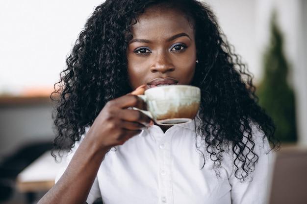 Portret piękna amerykanin afrykańskiego pochodzenia kobieta pije kawę