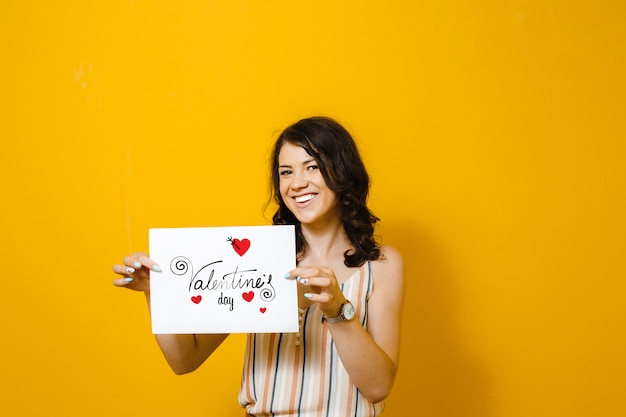 Portret piękna azjatycka dziewczyna trzyma białego puste miejsce w jej rękach z sercem nad kolor żółty ścianą