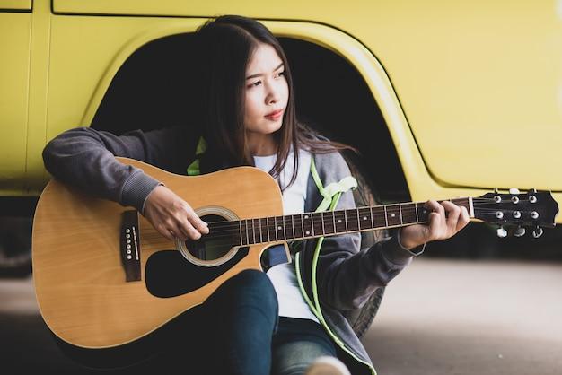 Portret piękna azjatycka kobieta trzyma gitarę akustyczną