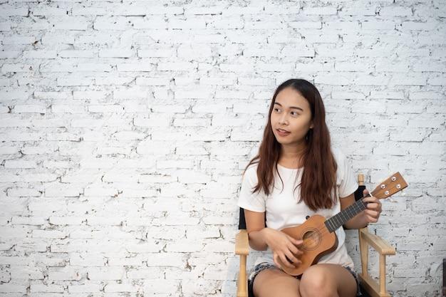 Portret piękna azjatykcia dziewczyna bawić się gitarę na bielu z kopii przestrzenią