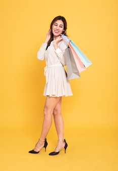 Portret piękna azjatykcia dziewczyna jest ubranym smokingowych mień torba na zakupy na żółtym tle.