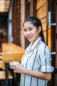 Portret piękna azjatykcia kobieta relaksuje przy kawiarnią