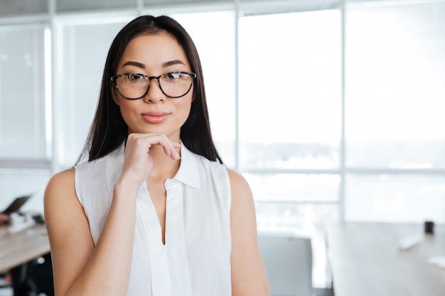 Portret piękna azjatykcia młoda bizneswoman pozycja w biurze