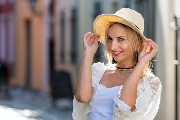 Portret piękna blond kobieta z słońce kapeluszem ubierał w świetle odziewa. modna dziewczyna pozuje w tle ulicy