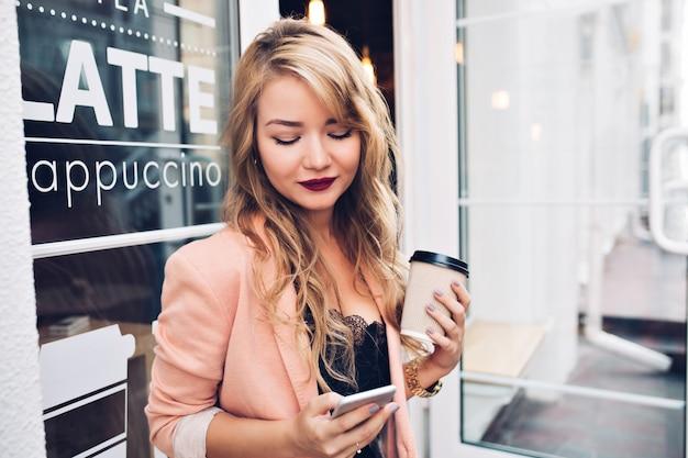 Portret piękna blondynka na tarasie przy filiżance kawy. nosi koralową marynarkę, winne usta, uśmiecha się do telefonu w dłoni.