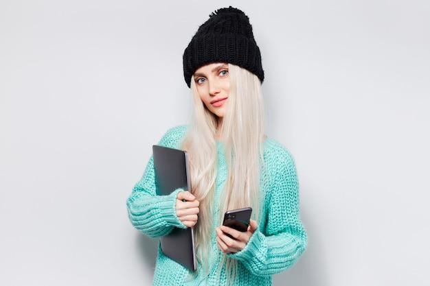 Portret piękna blondynka trzyma smartfona i laptopa