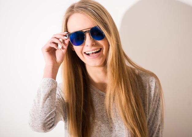 Portret piękna blondynki dziewczyna z okularami przeciwsłonecznymi jest uśmiechnięta