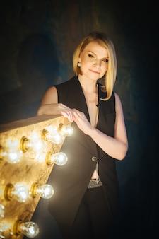 Portret piękna blondynki młoda kobieta na tle gwiazda z lampami.
