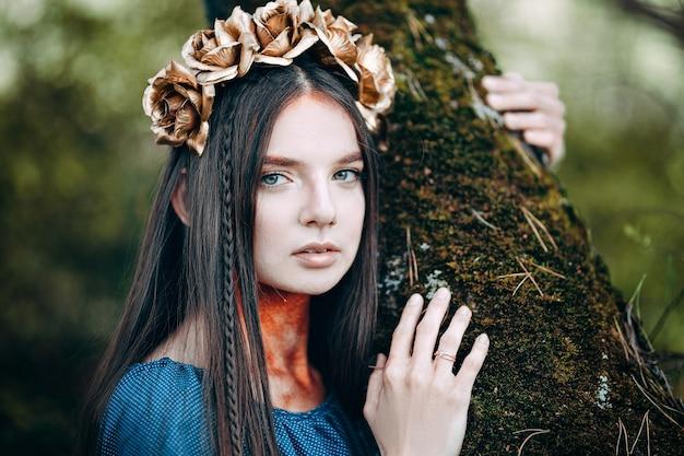 Portret piękna brązowowłosa kobieta w błękit sukni, z wiankiem złoty róż bajki las