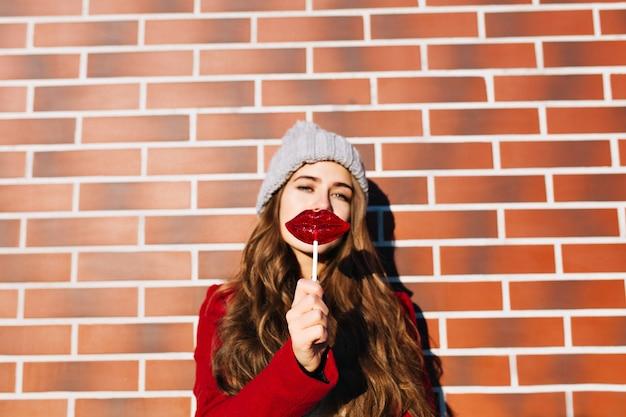 Portret piękna brunetka dziewczyna z ustami lizaka na ścianie na zewnątrz. nosi dzianinową czapkę, czerwony płaszcz.