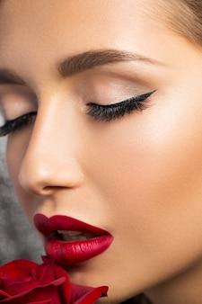 Portret piękna brunetka z czerwoną różą