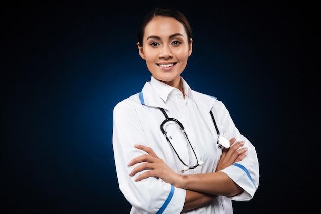 Portret piękna brunetki pielęgniarka odizolowywająca nad czernią