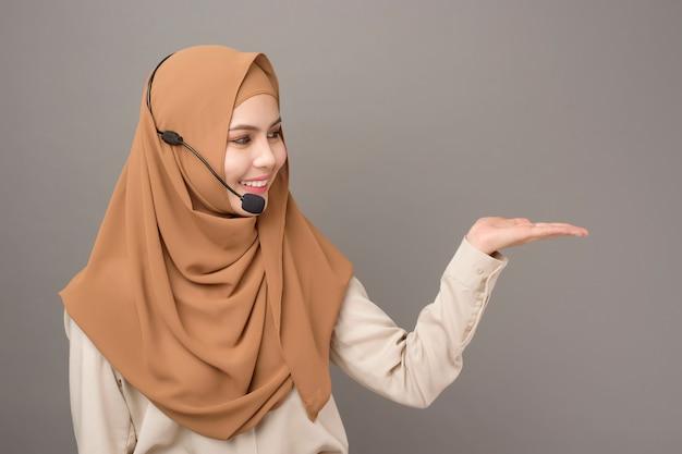 Portret piękna centrum telefoniczne kobieta z hijab na szarość