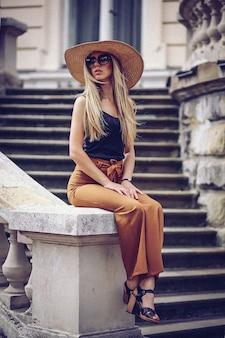 Portret piękna chłodno dziewczyna gestykuluje w kapeluszu i okularach przeciwsłonecznych nad grunge ścianą
