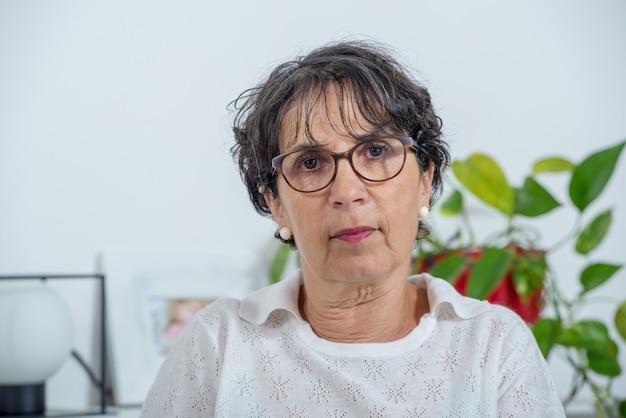 Portret piękna dojrzała kobieta z eyeglasses w domu