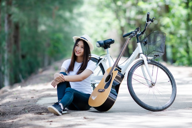 Portret piękna dziewczyna bawić się gitarę z rowerem przy naturą