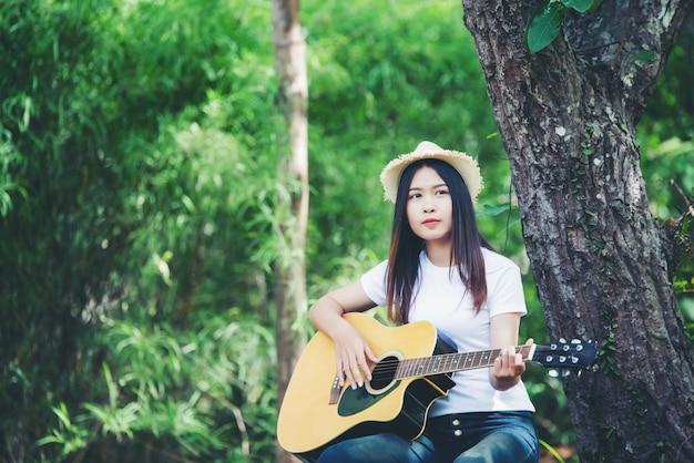 Portret piękna dziewczyna bawić się gitarę z writing przy naturą