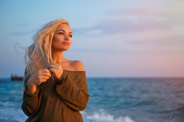 Portret piękna dziewczyna na plaży przy zmierzchem.