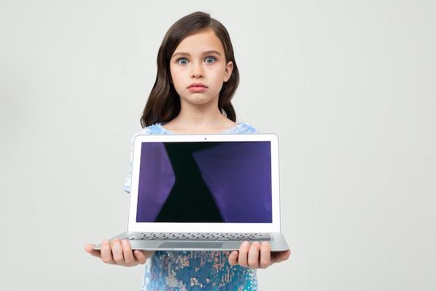 Portret piękna dziewczyna trzyma laptop z pustym ekranem wkładać stronę internetową na białej ścianie z kopii przestrzenią