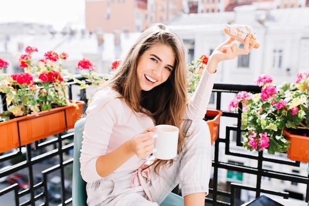 Portret piękna dziewczyna z długimi włosami jedząc śniadanie na balkonie otaczają kwiaty rano w mieście. trzyma kubek, rogalika, bawi się.
