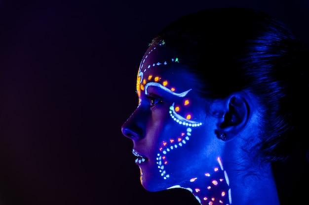 Portret piękna dziewczyna z pozafioletową farbą na jej twarzy. dziewczyna z neonowym makijażem w kolorowym świetle.