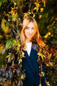 Portret piękna dziwna młoda dziewczyna z czerwonym włosy i uroczą twarzy pozycją w lianach w lesie w pogodnym jesień dniu. piękno młodości. spadają wielokolorowe liście. kobieta w płaszczu mody. krzewy i drzewa