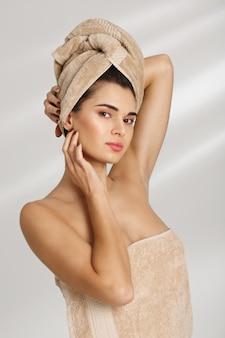 Portret piękna elegancka młoda kobieta po kąpielowej pozyci zakrywającej w ręczniku.