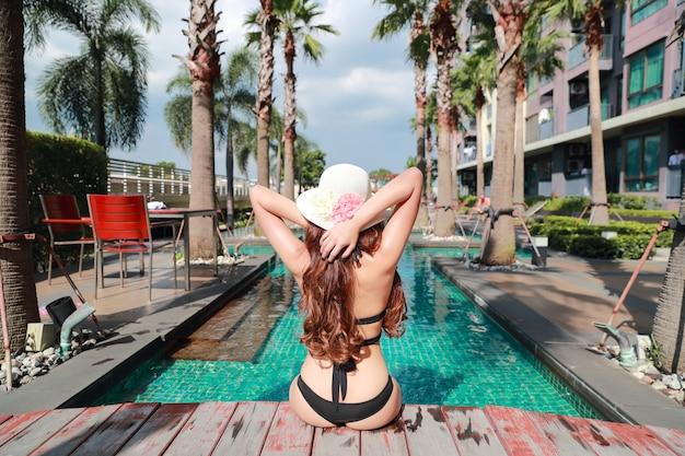 Portret piękna i seksowna kobieta cieszy się wakacje wakacje w pływackim basenie