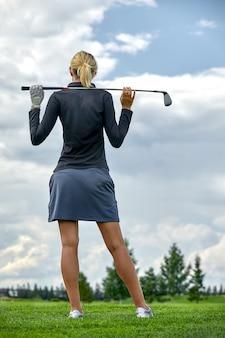 Portret piękna kobieta bawić się golfa na zielonym polu outdoors