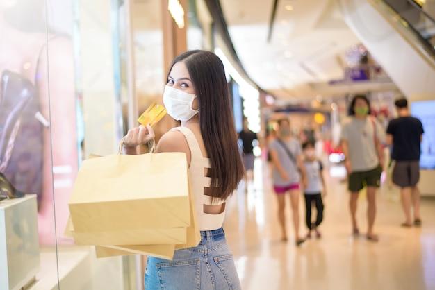 Portret piękna kobieta jest ubranym twarzy maskę w centrum handlowym