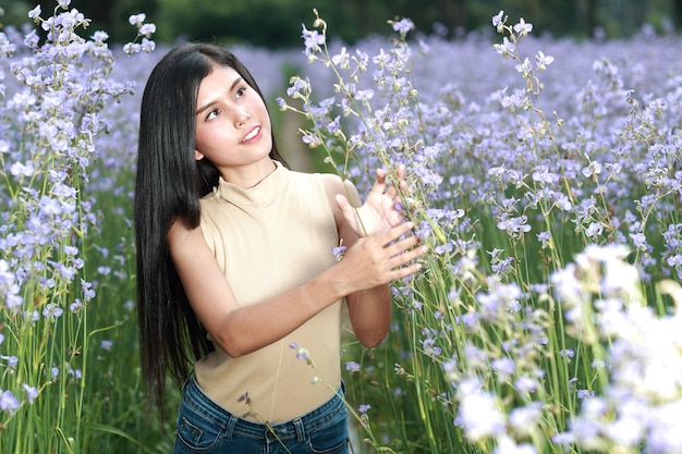 Portret piękna kobieta ma szczęśliwego czas i cieszy się wśród kwiatu czubatego pola w naturze