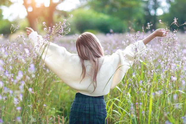 Portret piękna kobieta ma szczęśliwego czas i cieszy się wśród kwiatu naga-czubatego pola w naturze