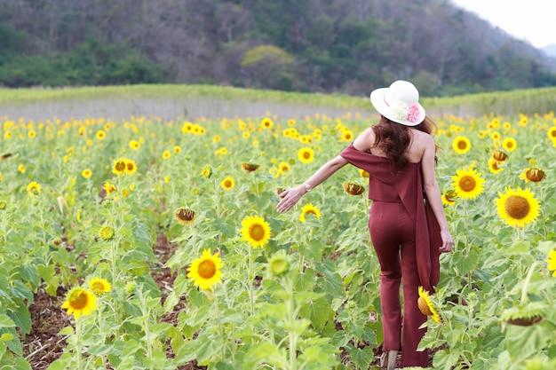 Portret piękna kobieta ma szczęśliwego czas i cieszy się wśród słonecznika pola w naturze