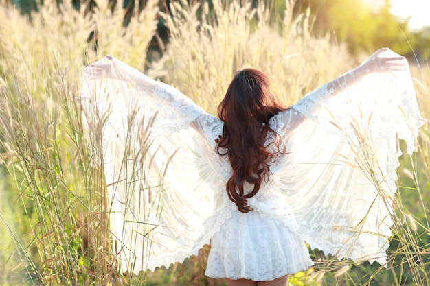 Portret piękna kobieta ma szczęśliwego czas i cieszy się wśród trawy pola w naturze