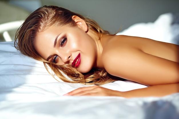 Portret piękna kobieta na łóżku w ranku