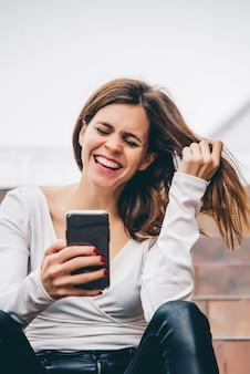 Portret piękna kobieta ono uśmiecha się patrzejący jej telefon