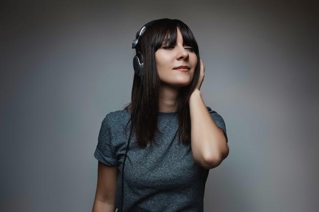 Portret piękna kobieta pozuje z hełmofonami