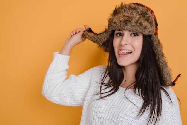 Portret piękna kobieta ubierał w futerkowym kapeluszu w studiu