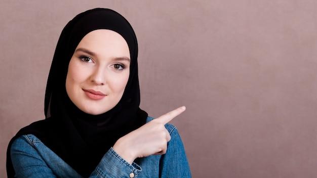 Portret piękna kobieta wskazuje przy stroną